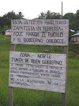 La pancarte indique en espagnol : « Vous vous trouvez en territoire rebelle zapatiste. Ici le peuple commande et le gouvernement obéit. Zone nord. Conseil de bon gouvernement. Le trafic d'armes, la production et la consommation de drogues, de boissons alcoolisées et les ventes illégales d'essences d'arbres sont strictement interdites. Non à la destruction de la Nature. » (Photo prise en 2005 sur l'autoroute 307, au Chiapas)